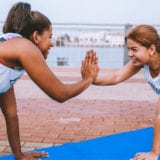 Two woman high fiving in a plank position on a yoga mat.